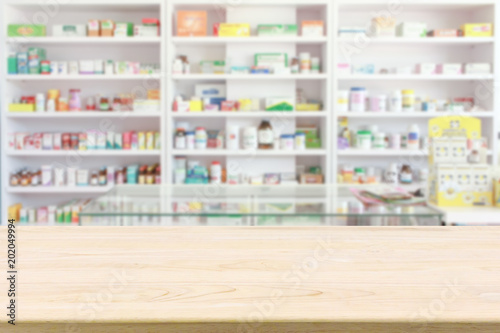 Photo sur Toile Pharmacie Pharmacy drugstore counter table with blur abstract backbround with medicine and healthcare product on shelves