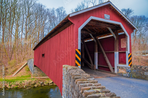 Valokuva Outdoor view of red covered bridge inside of the forest in Lancaster