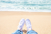 Female Feet In Jeans And White Sneakers On Beach. Walk Along The Beach