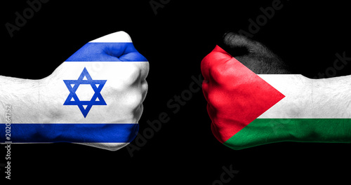 Fotografie, Obraz  Flags of Israel and Palestine painted on two clenched fists facing each other on