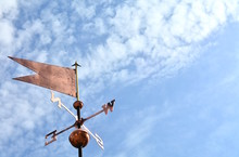 The Weathervane In The Blue Sky With Some Clouds.