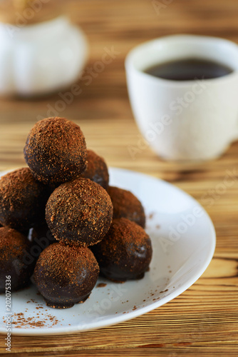 Fotografie, Obraz  Chocolate petit fours on a wooden table with a cup of coffee
