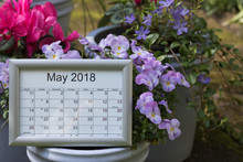 Calendar Of The Month Of May 2018 Is Among Spring Flowers & Pots In A Garden. Lunar Days Are Important For Gardening.