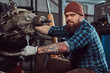 A brutal tattooed bearded mechanic specialist repairs the car engine which is raised on the hydraulic lift in the garage. Service station.