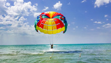 Happy Couple Parasailing On Beach In Summer. Couple Under Parachute Take Off Hanging Mid Air. Having Fun. Tropical Paradise. Positive Human Emotions, Feelings, Family, Children, Travel, Vacation