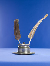 Quill Pens And Inkwell On Blue Background