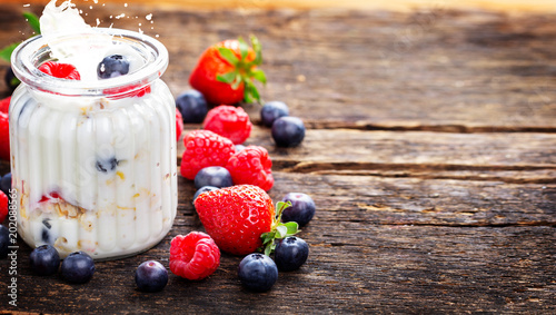 Yogurt with berries and cereals - healthy breakfast on wooden table