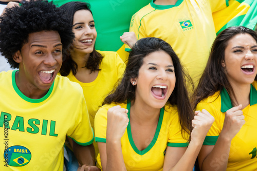 Photo  Cheering brazilian soccer fans with flag at stadium