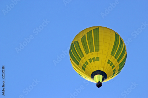Poster Luchtsport Yellow air balloon on the blue sky background. View from bottom
