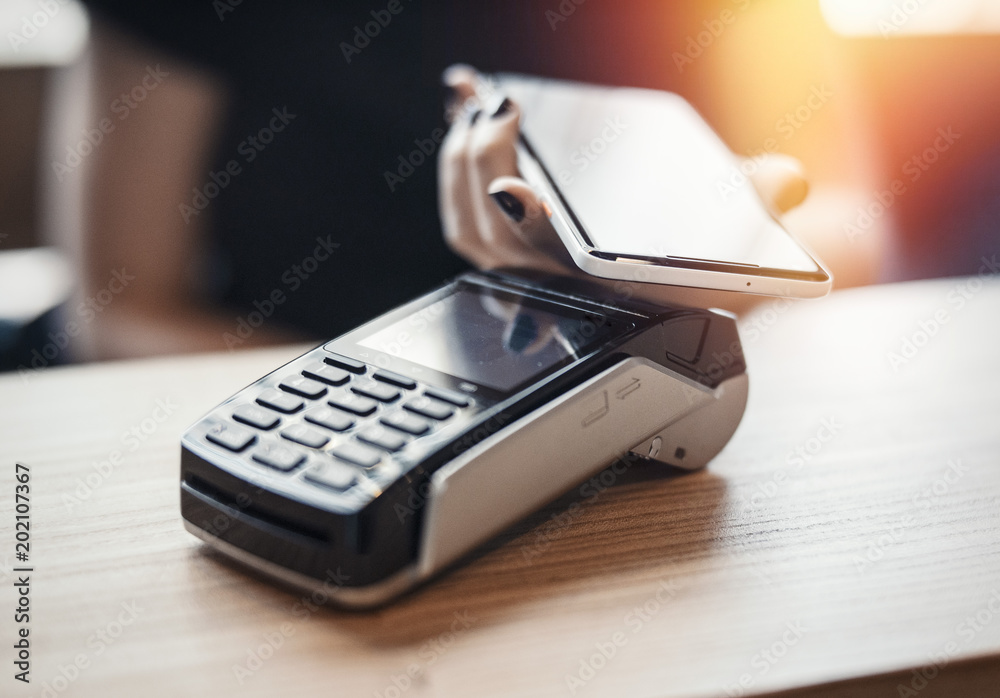 Fototapeta Young woman pays via payment terminal and mobile phone.