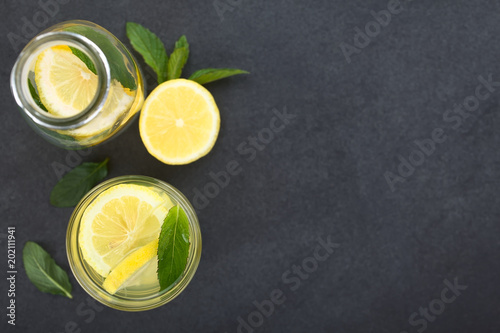 Fresh homemade lemonade with mint leaves, photographed overhead on slate (Selective Focus, Focus on the top of the lemonade)
