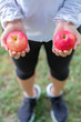 young fitness woman holding in hands red apple and donut, female choose between fruit is Healthy food and sweet is unhealthy junk foods. Dieting, obesity, eating lifestyle and nutrition concept