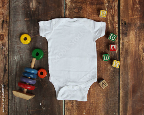 d8c0c8ca3177 Mockup Flat Lay of white baby bodysuit shirt on rustic wood ...