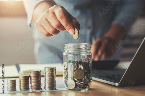 Fototapeta businesswoman hand puting coins in glass for saving money. concept finance and accounting obraz
