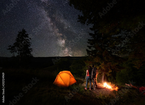Photo Stands Camping Rear view of young couple tourists enjoying the starry sky with a bright Milky way under the mighty trees near the campfire and orange illuminated tent in mountains. Romantic night camping near forest