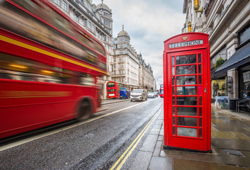Fototapeta London, England - Iconic blurred vintage red double-decker bus on the move with traditional red telephone box in the center of London at daytime