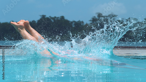 CLOSE UP: Unrecognizable girl dives into crystal clear pool on hot summer day Wallpaper Mural