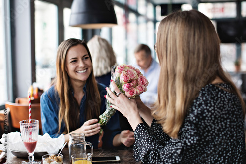 Smiling young woman giving fresh flower bouquet to female friend sitting at restaurant