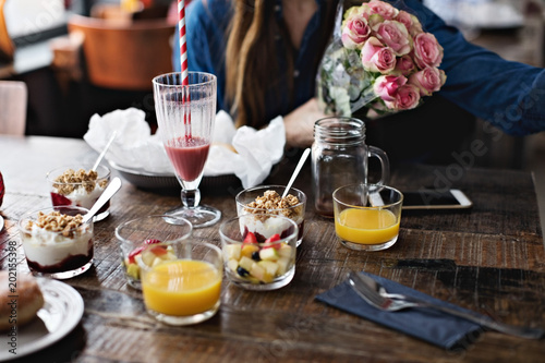 Midsection of woman sitting with flower bouquet by food on dining table at restaurant