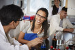 Smiling young multi-ethnic chemistry students with solutions at laboratory in university