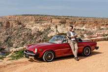 An Attractive Handsome Man Mate Is Leaning On A Retro Car In A Classic Suit On A Sunny Afternoon On A Sandy Desert Road