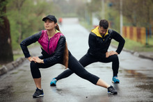 Two Friends Sportsmen Stretching And Warming Up At Rainy Day