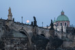 The moon rises over the famous Charles bridge in Prague old town in Czech Republic capital city during twilight