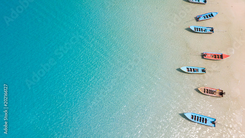 Cadres-photo bureau Vue aerienne Aerial: Shoreline with thai fishing boats and long tail taxi boats parking along the sand beach of Thailand