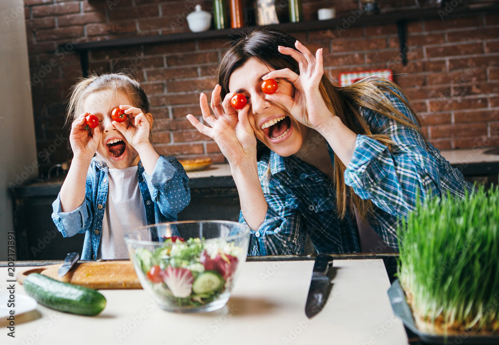 Fototapety, obrazy: Mother cook with daughter on kitchen,take fun with tomatoes.