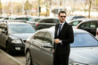 successful and handsome man in suit outside with his expensive car
