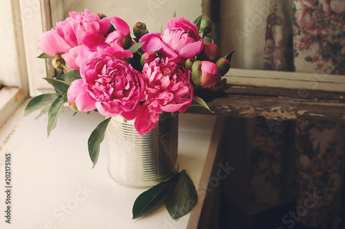 lovely pink peonies bouquet in vase on rustic white wooden background at window, space for text. top view. floral greeting card. happy mothers day. spring image. shabby chic concept