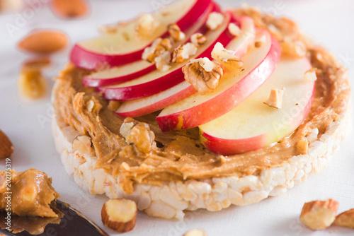 Fotografía  Apple crisp bread toast with apple slices, peanut butter, almonds and walnuts