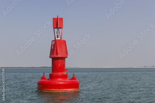 Fotografie, Obraz Floating red navigational buoy on blue sea