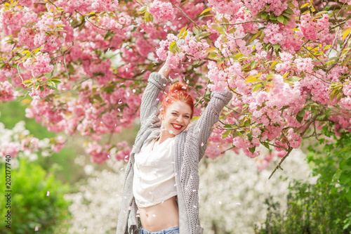 Fotografie, Obraz  Beautiful young woman with red hair having fun standing in cherry blossom tree,