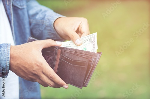 Fotografía  Businessman Person holding an wallet in the hands of an man take money out of pocket