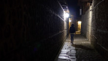 Lonely Woman Walk In Old Stone Pavement Alley At Night In The Back Street