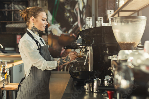Fotografie, Obraz  Tattooed barista making coffee in professional coffee machine