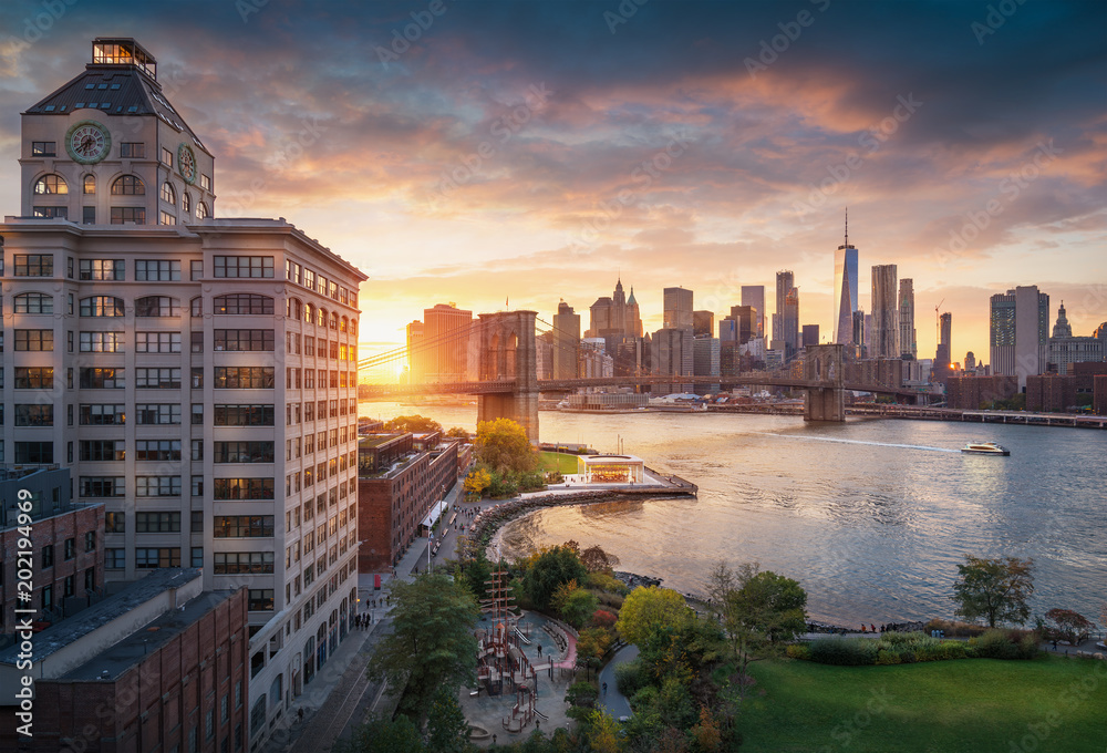 Fototapety, obrazy: Famous Brooklyn Bridge in New York City with financial district - downtown Manhattan in background. Sightseeing boat on the East River and beautiful sunset over Jane's Carousel.