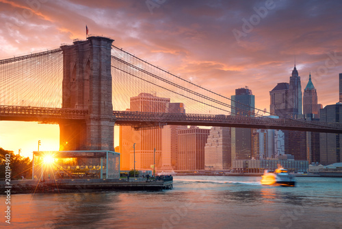 Foto auf Gartenposter Brooklyn Bridge Famous Brooklyn Bridge in New York City with financial district - downtown Manhattan in background. Sightseeing boat on the East River and beautiful sunset over Jane's Carousel.