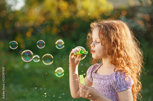Poster Artist KB Little curly girl blowing soap bubbles.