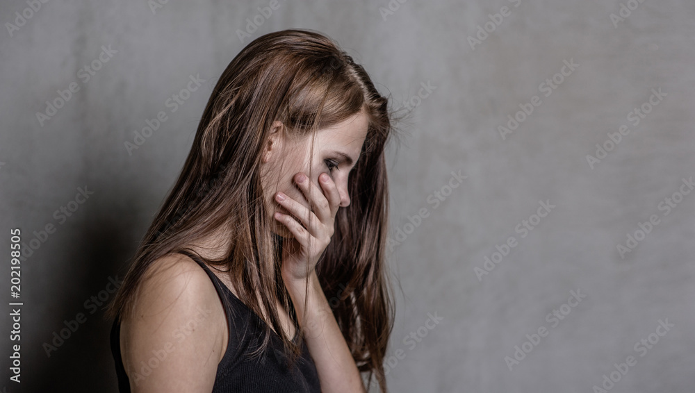 Fototapeta crying teen girl covers her mouth with her hands. Space for text