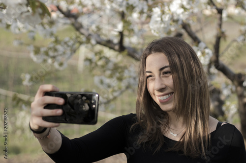 Authentic girl with a black t-shirt taking a selfie. Green natural background.