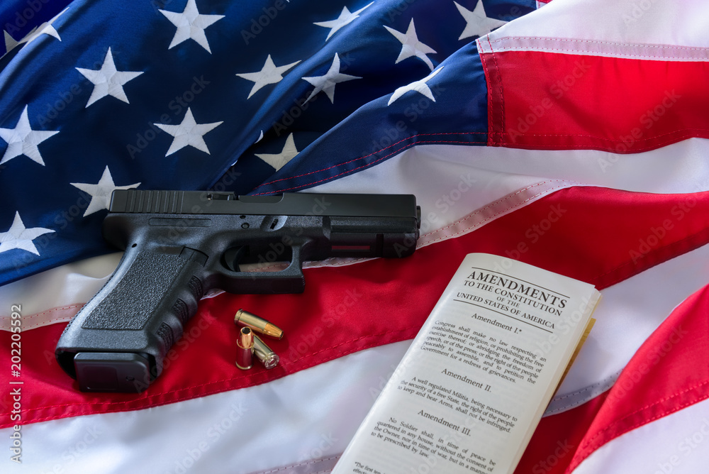 Fototapeta The second amendment and gun control in the US, concept. Handgun, bullets, and the american constitution on the USA flag.