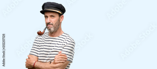 Fotografía Sailor captain man smoking a tobacco pipe with crossed arms confident and happy