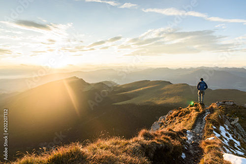 Fototapeta Silhouette of the man on top the peak of mountain on sunrise sky , Sport and active life conceptual design. obraz