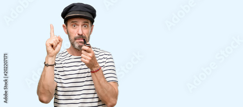 Sailor captain man smoking a tobacco pipe happy and surprised cheering expressing wow gesture pointing up isolated over blue background