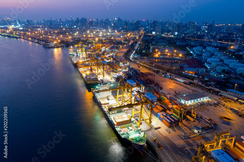 Fototapeta Containers yard in port congestion with ship vessels are loading and discharging operations of the transportation in international port.Shot from drone. obraz na płótnie