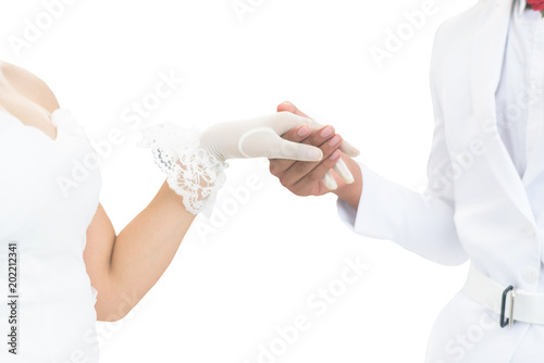 Vászonkép Asian bride in white wedding dress and groom in white suit holding hands isolate