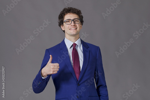 Valokuva Curly-headed boy smiling and showing big thumb up