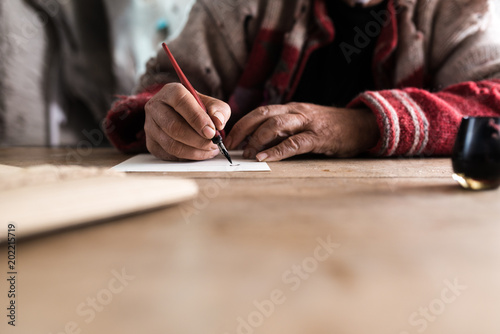 Fotografie, Obraz  Old man with dirty hands writing a letter using a nib pen and ink
